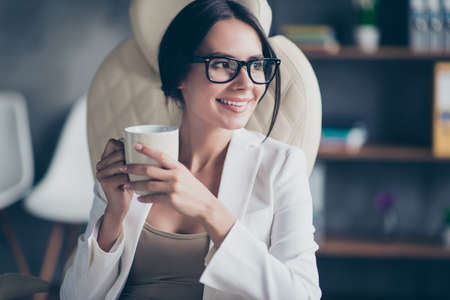 Portrait of cheerful delighted with toothy smile business woman dressed in white jacket is having a pause and holding cup of fresh aromatic latte Stock Photo