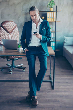 Full length portrait of busy rich director   leaning  on table in work station, holding a smart phone in hand, reading emails