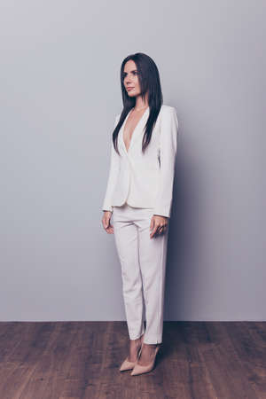 Its white theme party and meeting! Full-length half-turned portrait of successful stunning beautiful rich brunette woman wearing white smart clothes, isolated on grey background