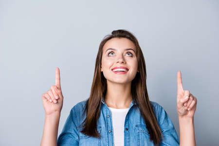 Junge glückliche Frau im Jeanshemd, das oben schaut und oben zeigt, möchte etwas interessantes zeigen und steht über grauem Hintergrund