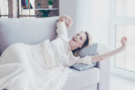 Beautiful lovely wonderful pretty young woman is having a nap in a sofa, she is stretching herself and yawning