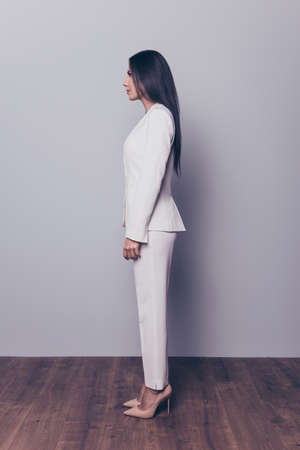 Full-length vertical profile side view portrait of smiling happy confident lady with long black hair wearing beige high heeled shoes and white suit, isolated on grey background