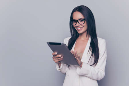Confident user digital tablet. Portrait of cheerful joyful beautiful gorgeous with beaming toothy smile holding tablet and reading the latest news on internet, isolated on grey background, copyspace 版權商用圖片