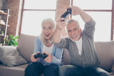 Middle-aged couple excited passionate about car racing game, sitting on a couch in their house in front of the tv screen playing with joysticks, very emotional