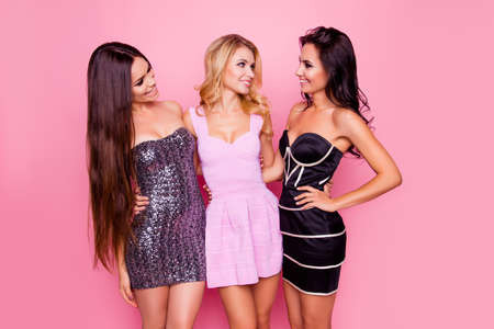 Portrait of three cute, nice, slim, attractive girls, in short dresses, looking to each other, having fun on new year party, standing over pink background
