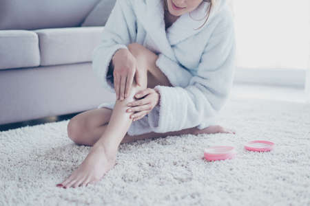 Cropped close up photo of woman wearing white bathrobe, she is sitting on the floor and applying moisturizing cream on her legs and nails after depilation and taking a shower Zdjęcie Seryjne