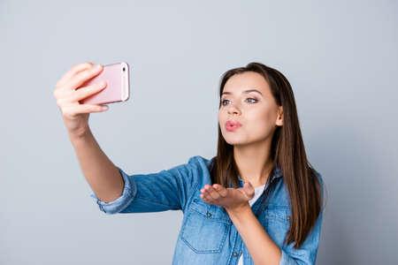 Sluit omhoog portret van sexy onderneemster, student die, freelancer selfie op haar smartphone maken en kus blazen aan de voorcamera terwijl status over grijze achtergrond