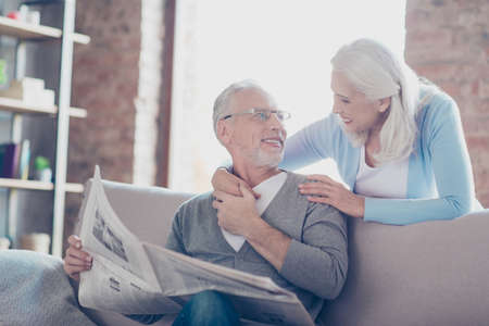So lovely and tender old couple! A grandfather is reading a newspaper and telling the latest news to his lovable wife who is hugging him