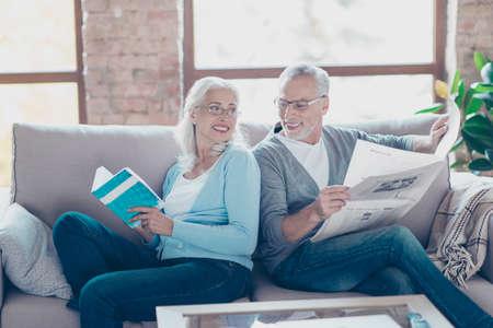 年金受給者は安静時、本や新聞を読みながらリラックスします。ソファに座って、お互いに笑みを浮かべて 写真素材