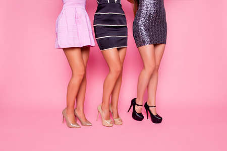 Side view portrait of  three beautiful girls in dress showing their smooth legs on pink background Reklamní fotografie