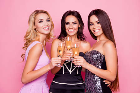 Portrait of three amazing, cute, pretty, astonished girls in luxury short dresses holding glasses with champagne, spending  together new year party, standing over pink background 스톡 콘텐츠