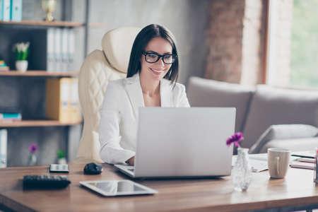 Linda confiante inteligente impressionante editor de revista elegante está digitando no laptop um novo artigo para a revista, ela está sentada no seu local de trabalho Foto de archivo