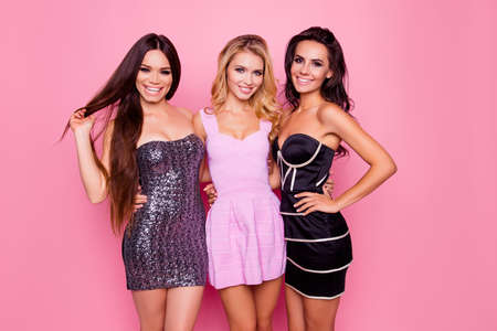 Portrait of three cute, nice best girlfriends, hugging each other on waist, posing for photo on someones birthday bachelor evening party, standing over pink background