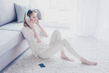 My mood depends on music! Charming relaxed careless beautiful woman is sitting on the floor, leaning on the sofa, listening to favorite tracks on her smartphone Stock Photo