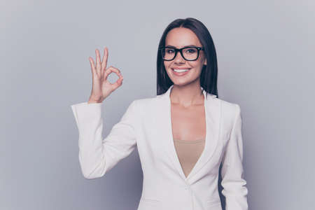 Pretty cheerful smiling cute lady wearing formal outfit and glasses is showing okay gesture, isolated on grey background