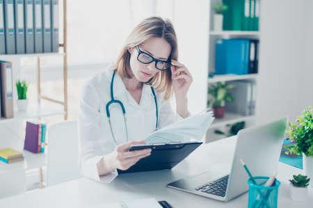 흰 코트와 안경에 숙련 된 자격을 갖춘 자신감을 갖춘 의사가 서류를 들고 분석하고 컴퓨터 앞의 탁자에 앉아 직장을 나간다.