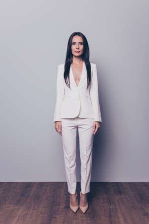 Full-length vertical front view portrait of beautiful attractive confident concentrated woman with dark hair wearing white elegant suit, she is staying still against grey background