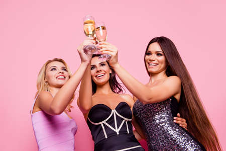 Low angle view portrait of attractive, charming, cheerful, happy, smiling, girls clinking their glasses with champagne on pink background