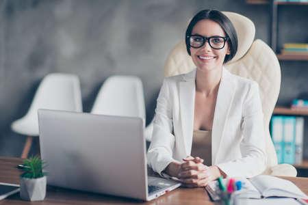 흰색 재킷을 입고 자신감 스마트 성공적인 아름 다운 사업가의 초상화, 그녀는 그녀의 워크 스테이션에서 컴퓨터 앞에 앉아있다 스톡 콘텐츠