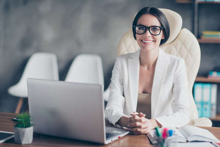 Portrait of confident smart successful beautiful businesswoman wearing white jacket, she is sitting in front on the computer at her workstation