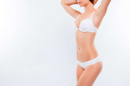 Concept of healthy lifestyle and nutrition, perfect skin and shape. Close up photo of ideal sexy woman's body wearing white brassiere and penties,  holding her hands, isolated on white background