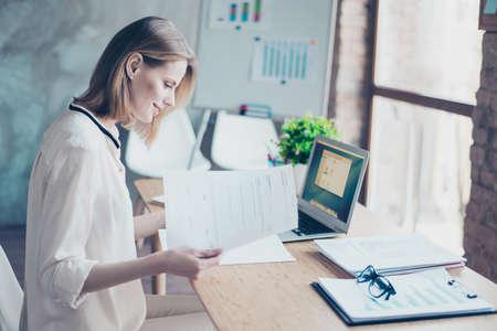 Drukke assistent zit op haar werkplek en controleert documenten
