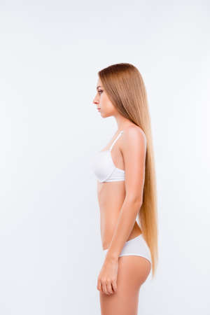 Vertical side view photo of young beautiful slim girl wearing white underwear, she has long smooth blonde hair, she is on a diet, isolated on white shadeless background
