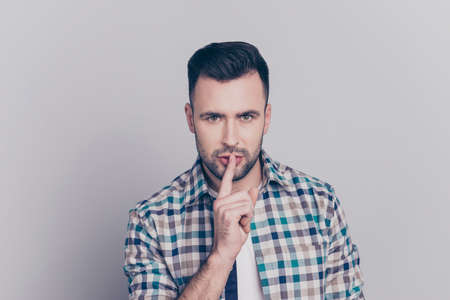 Shhh! Portrait of attractive man with bristle in checkered shirt holding finger on mouth showing hush silence sign