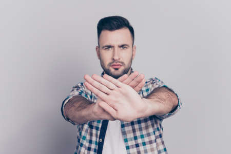 Prohibition symbol. Closeup portrait of young, serious man in checkered shirt making stop gesture with two crossed palms in front of himself on grey background