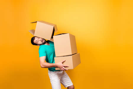 It's moving day! Busy funny guy in casual clothes is carrying big boxes in his hands and trying to keep one using his head