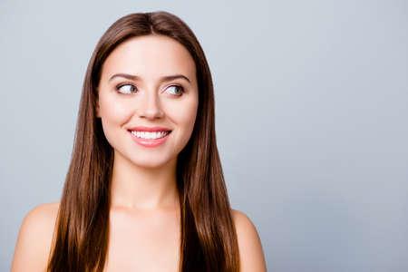 コピースペースを見つめる完璧な顔の肌を持つ若い笑顔の女性の肖像画をクローズアップ。 写真素材