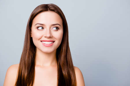 Close up portrait of young smiling woman with perfect face skin looking to the copy space.