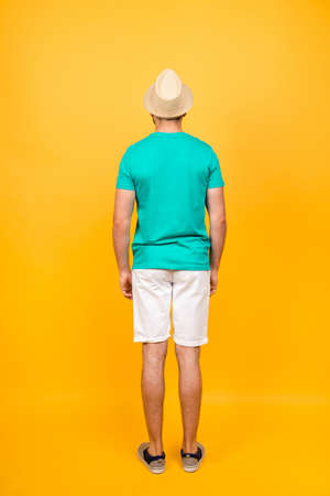 Vertical rear view portrait of man dressed in casual clothes, isolated on vivid yellow background Banco de Imagens