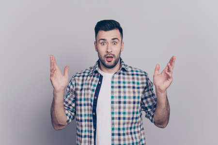 Portrait of surprised, joyful man in checkered shirt with wide opened eyes and mouth, raised his arms looking at camera, standing over grey background Stock fotó - 91279592