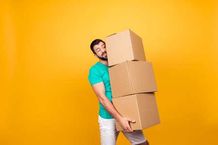 不機嫌なハンサムな男は、黄色の背景に隔離された彼の手に段ボール箱の大きなスタックを維持しようとしています