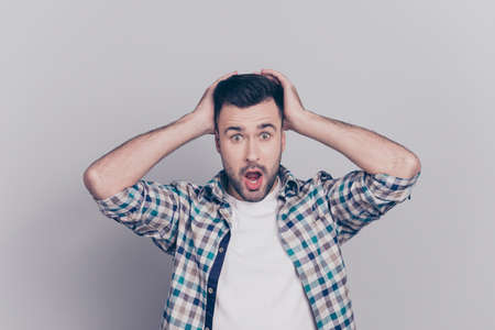 Portrait of surprised, shocked man with stubble and wide opened mouth and eyes in checkered shirt touching head with two hands isolated on grey background Stock Photo
