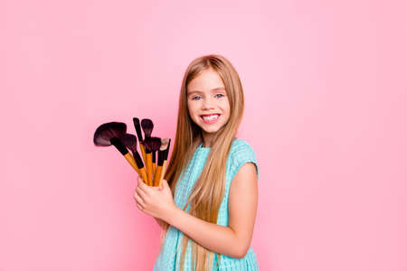 Cute charming sweet lovely delightful small girl with long straight blonde hair wearing blue dress is holding many brushes for doing make up, isolated on pink background