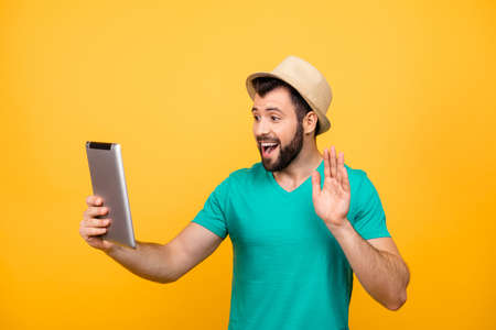 Cute happy excited joyful cheerful guy in casual clothes is using digital tablet for communication with his relatives, isolated on vivid yellow background Stock Photo