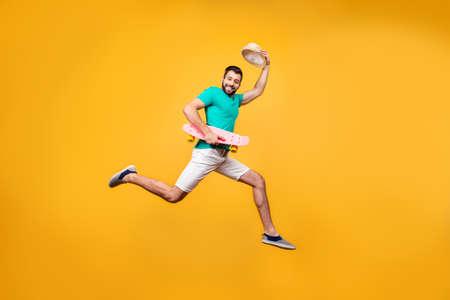おかしい陽気な喜んでいる男は彼の帽子を上げる彼の挨拶を送信する幸せな笑みを浮かべて、彼はジャンプ アップ手、背景が黄色の分離、copyspace スケート ボードと 写真素材 - 91279605