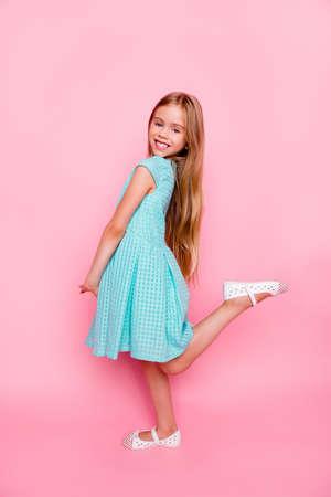 Vertical side view full-size, full-length portrait of cute lovely gentle tender little girl wearing light blue dress