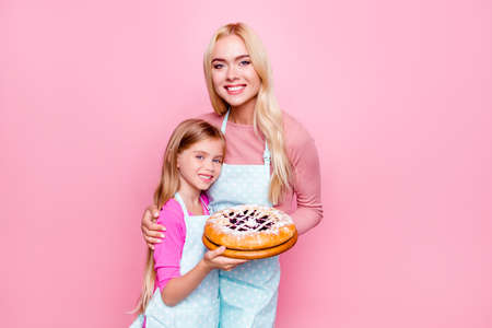 Studio portrait of happy mother and daughter holding together backed pie with jam inside for father Stock Photo
