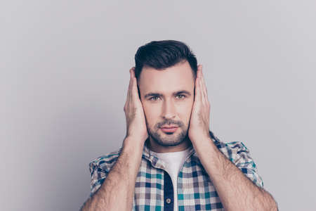 Close up portrait of young, attractive man in checkered shirt covering with hands his ears, he does not want to listen news, gossips, information, isolated over grey background Reklamní fotografie