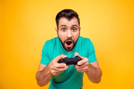 Close up portrait of funny joyful cheerful happy guy, he is rejoicing his victory with gamepad in hands, isolated on bright yellow background Reklamní fotografie