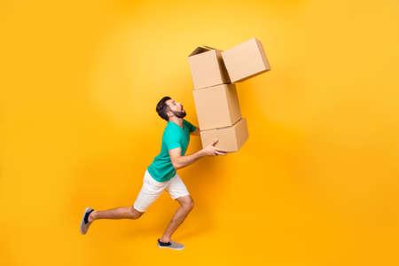 Zabawny zdenerwowany mężczyzna niesie swoje rzeczy w pudełkach do ostatnio kupionego mieszkania. Trzyma kartonowe pudła, a jeden spada