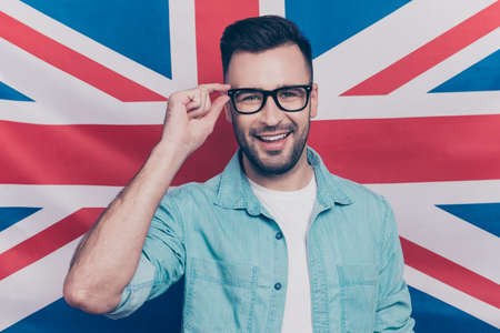 English language learning concept-portrait of cheerful man with bristle holding his hand on glasses standing over English flag background