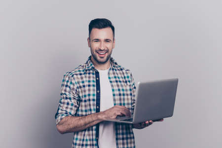 Portrait of bearded smiling brunet guy holding laptop, looking at camera, searching information through wifi, standing over grey background
