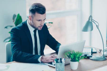 仕事の駅で彼の机に座って、ノート パソコンに情報を検索魅力的な集中して自信を持ってエレガントな弁護士の肖像画 写真素材