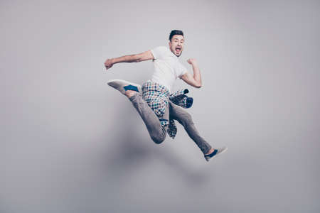 Happy young bearded attractive handsome man with opened mouth, jumping in air, triumphant, winner over grey background