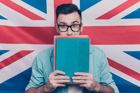 영어 학습 배경 - 영어 플래그 배경 위에 서있는 노트북과 반 얼굴을 닫는 손에 다채로운 복사 책을 들고하는 흥분된 남자의 초상화를 학습하는