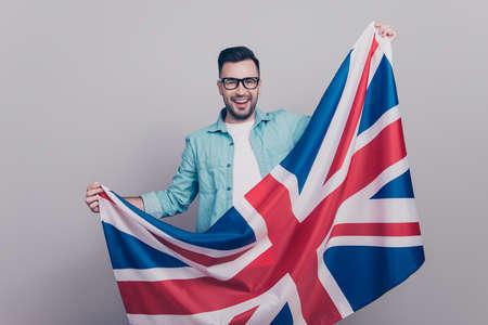 手を振る連合ジャックの旗を保持しているメガネ ・ ジーンズのシャツで魅力的でハンサムな男性の肖像画